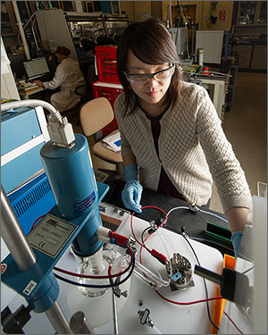 In this photo, a woman in safety glasses works in front of a device that includes plastic tubing and red and black wires.