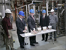 Photo of President George W. Bush and four men in research facility.