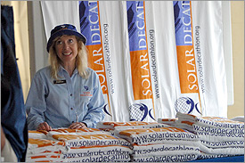 Photo of a smiling woman with long blond hair in a bucket cap behind several stacks of towels emblazoned with the Solar Decathlon name and logo. More of the same towels are draped behind her.