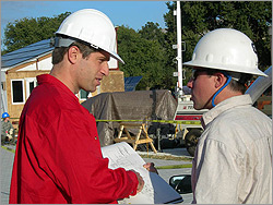 Photo of two men in hard hats speaking to each other with the construction site of the 2005 Solar Decathlon visible in the background.