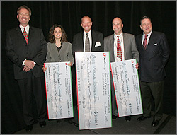 Photo of one woman and two gentlemen stand as a group on a stage with their award checks. Two presenters stand with them, one on each side of the group.