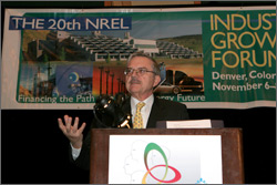 Photo of  a man standing at a podium giving a speech. Hanging on the wall behind him is the banner for NREL's 20th Industry Growth Forum.
