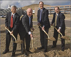 Photo of four men in suits holding shovels of dirt at a groundbreaking ceremony.