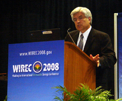 Photo of a man in a business suit speaking at a podium with a sign that reads www.WIREC2008.gov, WIREC 2008, Washington International Renewable Energy Conference.
