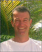 Photo of a man in a t-shirt smiling in front of palm leaves.