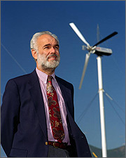 Photo of a man standing in front of a three-bladed wind turbine.