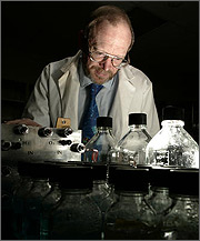 Photo of a man in lab coat, seated behind bottles and lab equipment.