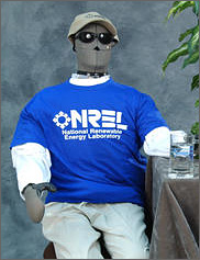 Photo of a manikin dressed in a National Renewable Energy Laboratory T-shirt sits on a chair next to a glass of water.
