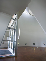 Photo of the angles of white interior walls in Science and Technology lobby with sunlight shining through large circular opening at top and through side window slits.  Light shines on red concrete floor in patterns.
