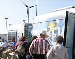 Photo showing two men and two women looking at science exhibits outside of a blue van with its side doors open. A three-bladed wind turbine sits beyond the van.