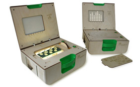 Photo of two wooden boxes with green handles lay side-by-side with their lids open. The box to the left is lit up with seven stoppers showing; the box to the right has not been assembled for testing yet.