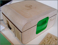 Photo of the box with the lid shut, revealing a green handle, the Lunchbox Lab logo, and a circular image carved into the lid.
