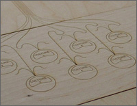 Photo of a carved wooden diagram that covers the area where the beakers will be placed during testing. The carving is of seven circles, depicting where each beaker will be placed.