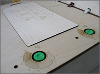 Photo of the box with the lid open before being set up for testing. The green embedded pressure sensor dials are shown next to the carved diagram of the beakers.