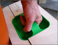 Photo of a hand grasping the green handle of the wooden Lunchbox Lab.