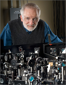 Photo of a man with a white beard wearing eyeglasses learning over a laboratory bench that is covered with tiny mirrors and precise measuring equipment to simulate sunlight in solar energy research.