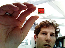 Photo close up of the hand of a young man.  The hand is holding up a transparent red solar cell mounted on a glass slide; the man's face is in the background.