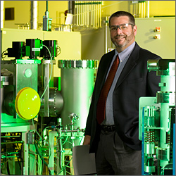 Photo of a man standing inside and smiling at the camera. He has very short hair and a closely trimmed beard. He is wearing clear safety glasses and a suit and tie. He is holding a report in one hand; his other hand is in his pocket. He is standing next to pressurized laboratory equipment, including cylinder-shaped vessels with thick metal lids attached with bolts. The equipment is connected by a series of thin metal tubes and valves.