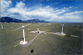 Photo of an aerial view of the National Wind Technology Center. Two wind turbines can be seen in the foreground, and mountains in the background. Research buildings are in the middle.