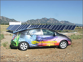 Photo of a small four-door car, viewed from the side, which is parked in front of a field of solar panels with jagged mountains in the background. The car is painted with images of a corn stalk and a wind turbine with 'Plug-In to Renewable Energy' written on the side panel.