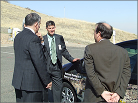 Photo of a man, wearing a gray suit, green shirt and green tie, who is talking to three men, in suits, with their backs to the camera. The man is facing the camera and has his left hand resting on the hood of NREL's research plug-in hybrid vehicle, which is parked in a lot.