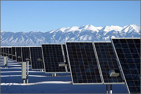 Photo of a series of large blue solar panels, framed in silver-colored metal, stretches toward the horizon in front of a background of snow-capped purple mountains under a clear, blue sky.