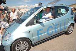 Photo of a light blue hatchback car parked outside in a parking lot. Onlookers and media watch as the driver, a man in a blue shirt and tie, reaches to the side for his safety belt. Text on the car side panel reads: driving the future, F-CELL.