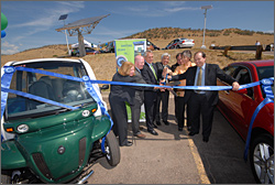 Photo of seven government officials, two women and five men, in business attire standing between two parked vehicles, a green car and a red car. The officials are jointly cutting a blue ribbon stretched in front of them with a large set of scissors