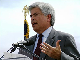 Photo of a man with silver hair, who is wearing a white shirt, dark blue tie and gray suit. He is speaking at a microphone while he gestures with his left hand. Just behind him is the top of a flag pole, capped by an American eagle, and a light blue sky. He is shown from the chest up. Some papers are visible on the podium in front of him.