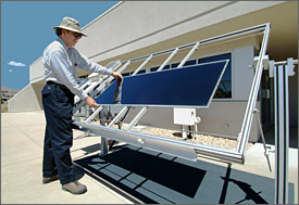 Photo of a man standing outside placing a solar panel for testing onto the standard outdoor measurement system, which looks like a metal scaffold tilted at an angle.