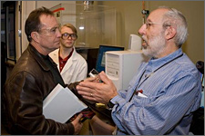 Photo of two men facing each in conversation. On the left, the man has brown hair and is wearing clear safety eyeglasses. He is wearing a brown leather jacket and carrying a bundle of white papers in his hand. He is listening to the man on the right, who is speaking intently and gesturing with his hands clasped together. He has short gray and white hair and a closely trimmed white beard. He is wearing a blue long-sleeved shirt. Behind them stands a row of scientific equipment covered in a clear hard plastic case and linked to a computer.