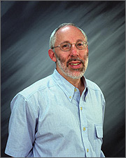 Photo of a man with thinning, short grey hair and a beard wearing a short-sleeved blue shirt and metal-rimmed eyeglasses, smiling at the camera.