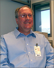 Photo of a man seated at a desk. He is wearing a blue shirt, a badge, and eyeglasses. He is smiling and has short hair.