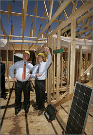 Photo of two men wearing hard hats stand in a house while it is being framed on a sunny day. Both men are wearing dress shirts and neckties. The man on the right is pointing up at the roof while the other man looks up. In the right foreground, a black solar panel rests tilted against a wall.