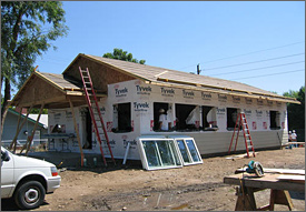 Photo of a small, rectangular house that is under construction on a dirt lot on a sunny day. Its roof and walls are framed. Its walls are sealed in a white house wrap. There are two windows lying on their side, tilted against the frame and waiting to be installed. A ladder is leaning against the house.
