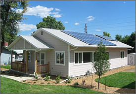 Photo of a small rectangular house with a front porch. It has tan siding and a light gray roof. On the roof are a large black flat array of solar panels and a small flat black array of solar panels. The sun is shining and a three foot roof overhang shades the windows on the south side of the house in the summer.