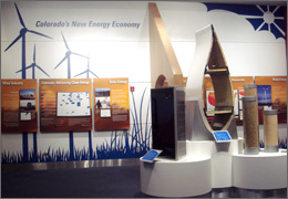 Photo of a front view of an exhibit on renewable energy. In the foreground is a pedestal featuring solar panels, a cross-sectional slice of a wind turbine blade and clear plastic tubes of dried plant material used to make biofuels. Mounted on the back wall are several colorful interpretive panels and maps explaining Colorado's renewable energy resources and industry. The wall also is painted with blue silhouettes of wind turbines, grass and the sun.