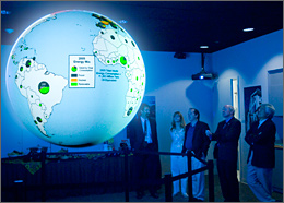 Photo of four men and one woman look up at a hanging globe of the Earth that shows light blue oceans and white continents with green and blue pie chart circles in each country. A key to the pie charts is visible although the text is not legible