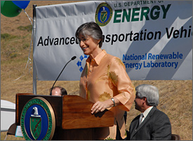 Photo of a gray-haired woman with eyeglasses wearing an orange outfit, who stands on a podium and speaks into a microphone. A banner with the DOE and NREL logos is behind her, as are two seated men.
