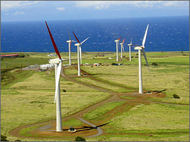 Aerial photo of seven large white wind turbines that form a wind energy farm in a green field on the coast of the island of Hawaii. The blue Pacific Ocean is in the immediate background, with a bank of puffy white clouds in the distance.