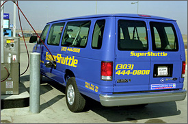 Photo of a blue passenger van with bright yellow letters fueling at a pump.