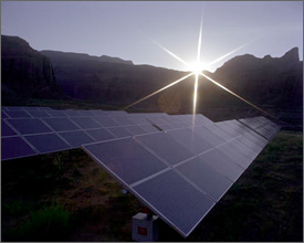 Photo of the sun rising over a mountain ridge to shine on a field of solar modules in the foreground.