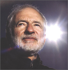 Photo of the head of a bearded, greying man who is looking into the distance with a sunburst behind him.