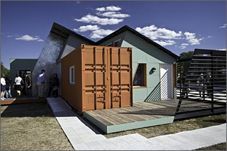 Photo of a small modular house featuring solar panels on its steeply-sloped roof.