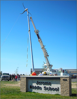 Photo of a wind turbine being hoisted upright by a crane while several people watch. Sign in the foreground reads Jerome Middle School.
