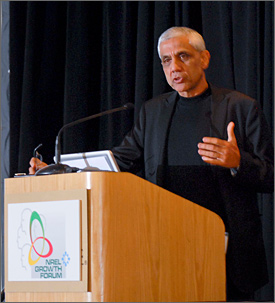 Photo of a man with short gray hair wearing a black suit speaking at a podium.