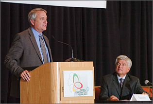 Photo of a gray-haired man wearing a gray suit speaking at a podium while a silver-haired man, seated at right, listens.