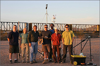 Photo of seven people standing outside in front of measurement equipment on a tripod.