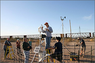 Photo of seven people working outside on equipment. A woman and a man stand on a ladder, and the woman adjusts equipment on a pole.
