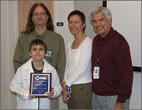 Photo of three adults standing with a boy and smiling. The boy is wearing a white lab coat and holding an awards plaque.